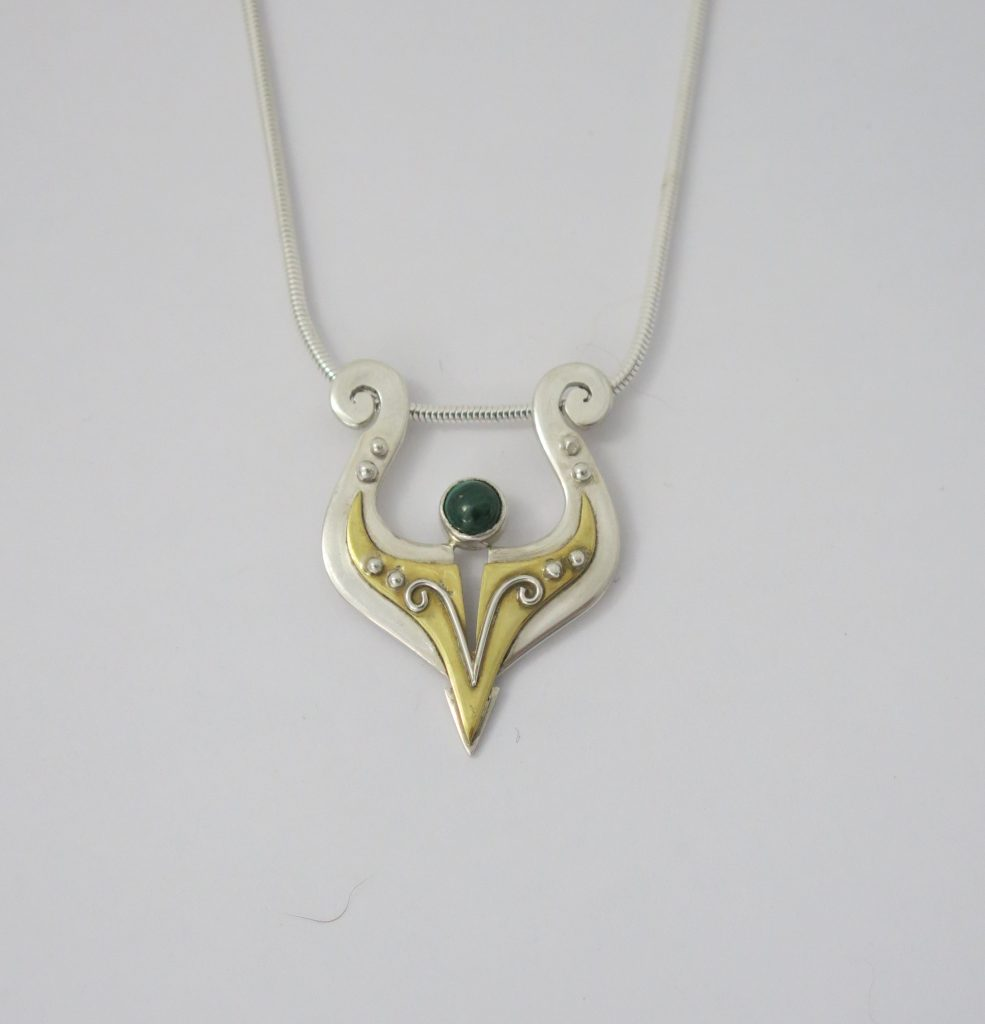 Silver and brass annular pendant by Hazel Morris
